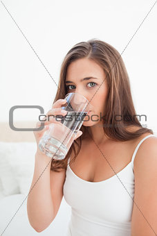 Close up, woman taking a drink from a glass while looking forwar