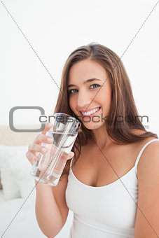 Woman smiling as she raises a glass near to her mouth