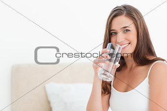 Woman smiles as she holds a glass to her mouth