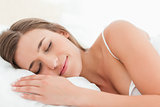 Woman in bed, sleeping and smiling softly