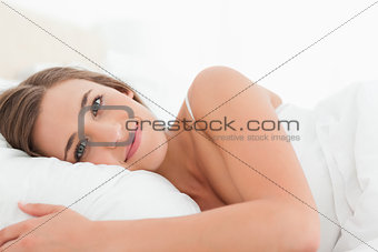 Woman lying in bed, eyes open and smiling