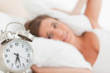 Woman with pillow over head head, as the alarm clock rings