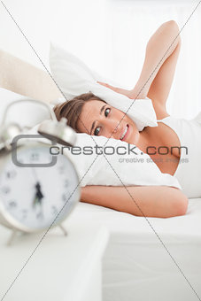 Woman covers her ears with a pillow and looks at her clock in an