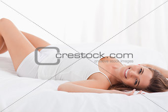 Woman lying on her back smiling while lying on the bed