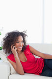 Woman smiling while making a phone call on the couch