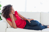 Woman lying on the couch making a call on her phone and smiling
