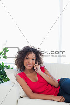 Close up, woman on the couch making a call and smiling