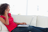 Woman making a call and using her laptop while on the couch smil