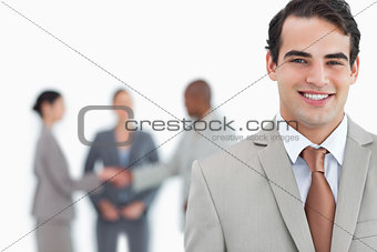 Smiling businessman with hand shaking colleagues behind him