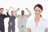 Smiling saleswoman with celebrating colleagues behind her