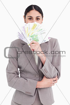 Young businesswoman hiding her face behind bank notes
