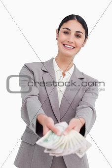 Smiling businesswoman handing over money