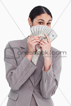 Young saleswoman hiding her face behind bank notes