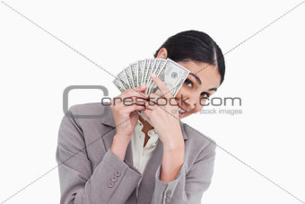 Young saleswoman covering her face with bank notes