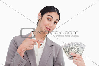 Saleswoman pointing at bank notes in her hand
