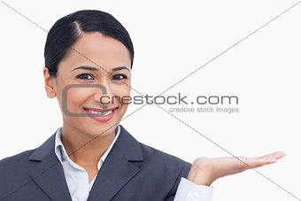 Close up of smiling saleswoman with her palm up