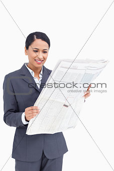 Close up of smiling saleswoman reading the news paper