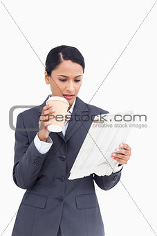 Close up of saleswoman with paper cup and news paper