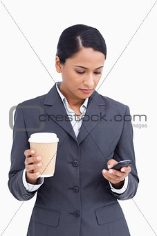 Close up of saleswoman with paper cup writing text message