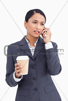 Close up of saleswoman with paper cup talking on cellphone