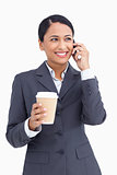 Close up of saleswoman with paper cup on her cellphone