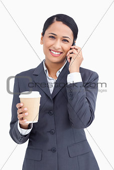 Close up of smiling saleswoman with paper cup and cellphone