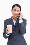 Close up of serious saleswoman with paper cup and cellphone