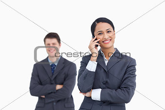 Close up of saleswoman on the phone with colleague behind her