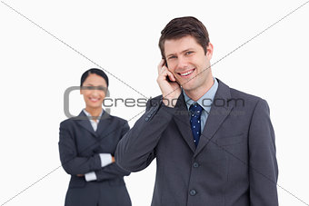 Close up of smiling salesman on the phone with colleague behind