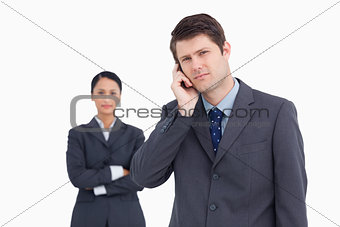 Close up of salesman on the phone with colleague behind him