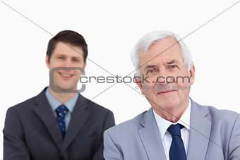 Close up of mature businessman with colleague behind him