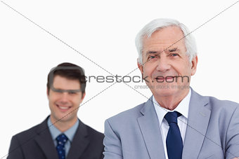 Close up of mature businessman with employee behind him