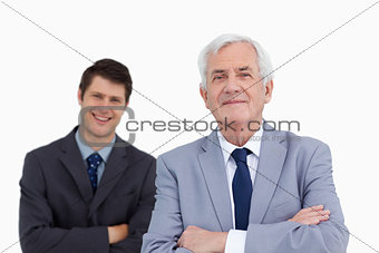 Close up of mature businessman with folded arms and colleague be