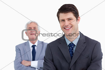 Close up of smiling businessman with his boss behind him