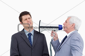 Close up of mature businessman with megaphone yelling at colleag