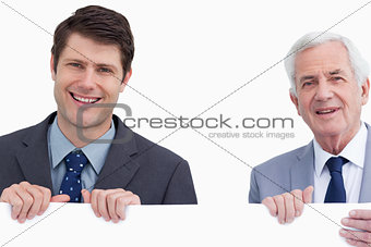 Close up of smiling businessmen holding blank sign