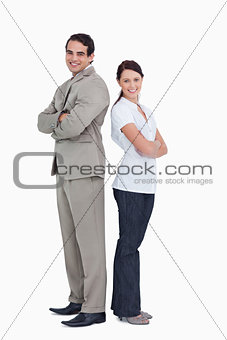 Smiling salesteam with arms folded standing back to back