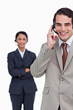 Smiling hotline employee with colleague behind him