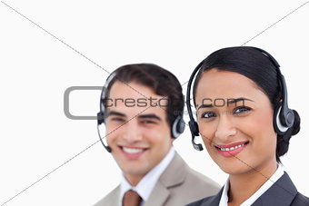 Close up side view of smiling telephone support employees at wor