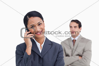 Smiling saleswoman on her mobile phone and colleague behind her
