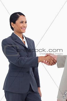 Smiling saleswoman shaking hand