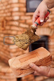 Masonry heater builder hand with brick and trowel