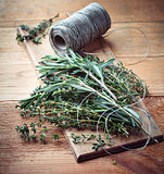 Fresh thyme and rosemary on wooden board