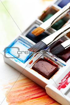Set of watercolors with brushes
