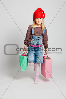 Smiling girl carrying Christmas shopping bags