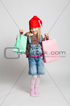 Happy young girl carrying Christmas shopping bags