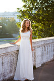 Elegant bride in a white dress near to white old concrete fence
