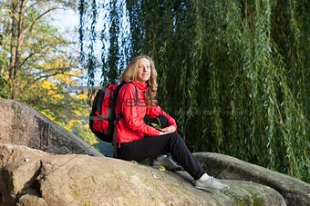 Woman backpacker enjoying relaxation on a halt in rocks
