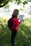 Young backpacker read the map among the sunny nature