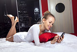 woman lying on bed with mobile phone l